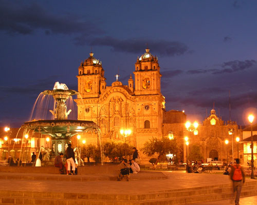 One of the must see destinations in South America: Fountain and colonial buildings in Cusco at night.
