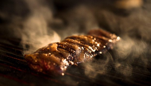 Close up of meat being cooked on a grill - Asado