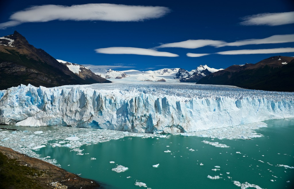 water in front of a wide, large glacier el calafate in patagonia
