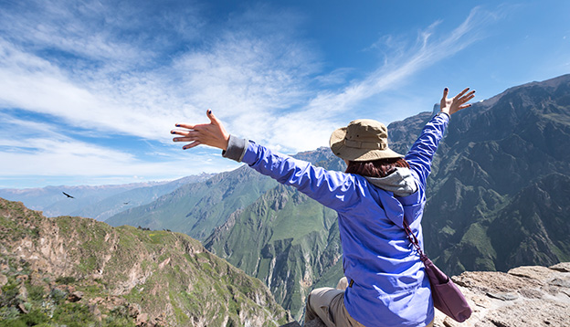 traveller sitting on the summit bird watching at Colca Canyon