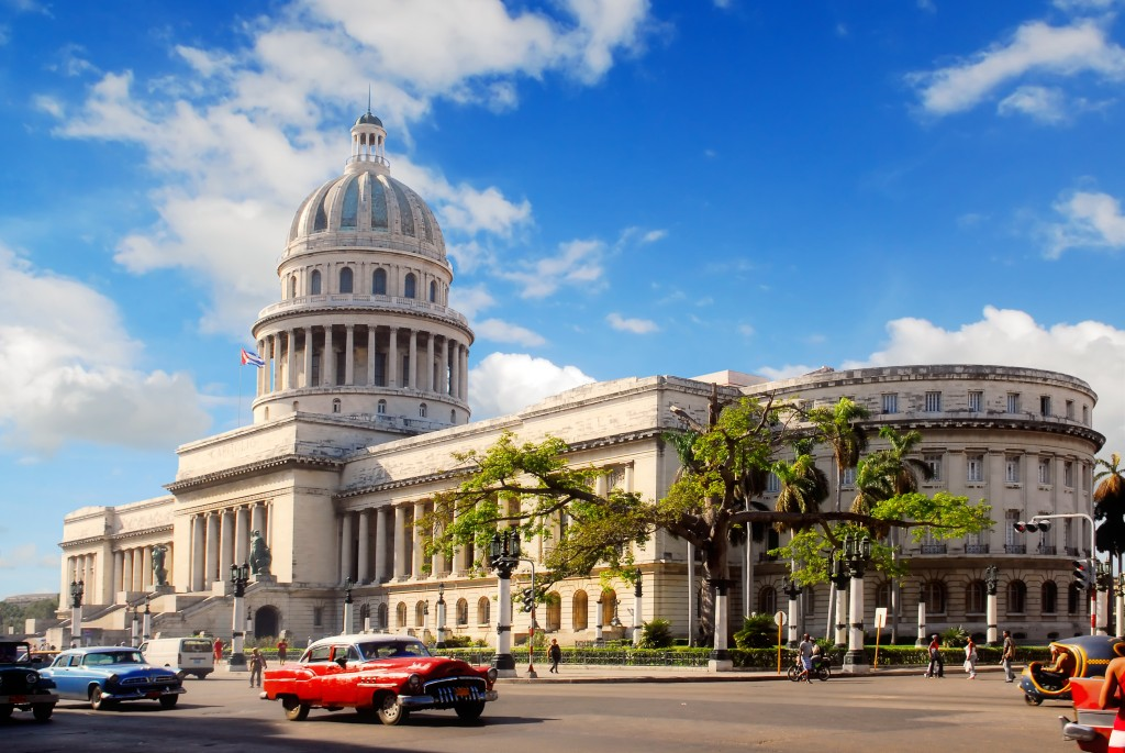 Classic american cars in front of hostoric building in Cuba