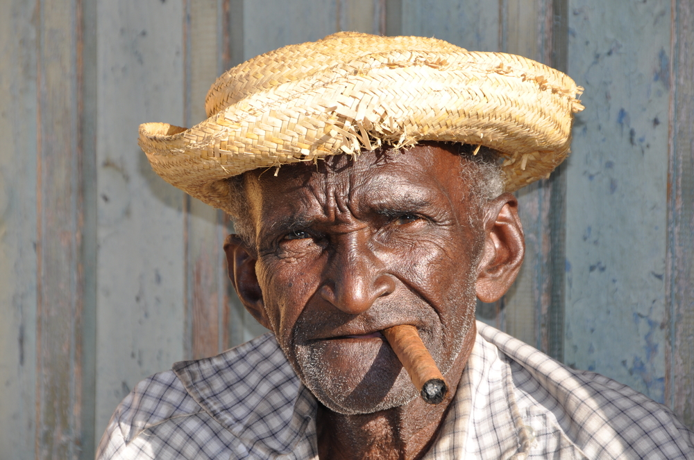 local man with hat smoking a cigar in Cuba