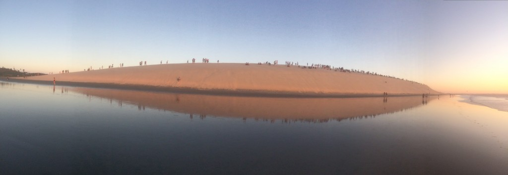 Sand dune next to water with people on it in Jericoacoara Brazil