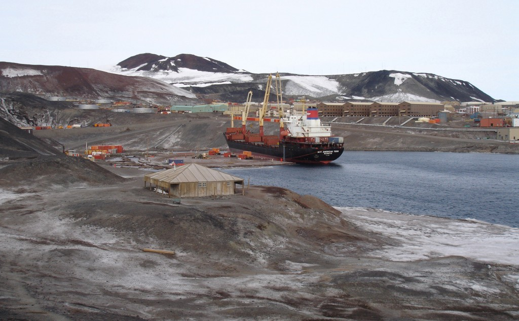 cargo ship in bay with mountains and snow