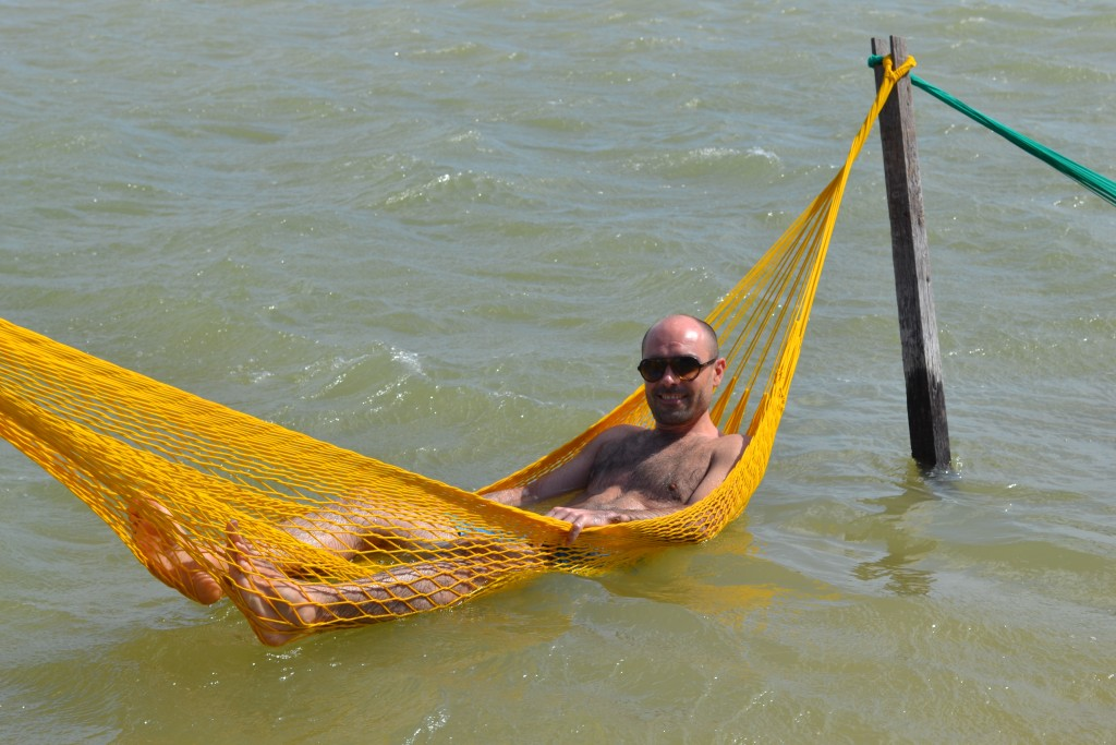 man in hammock in water in Lagoa Paradiso Brazil