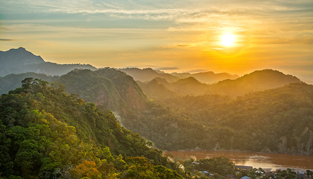 Sunset over lush green jungle covered hills with the Beni River visible in Rurrenabaque, Bolivia