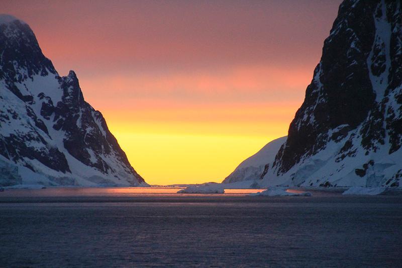 Weather in Antarctica: sunset between snowy mountains in antarctica