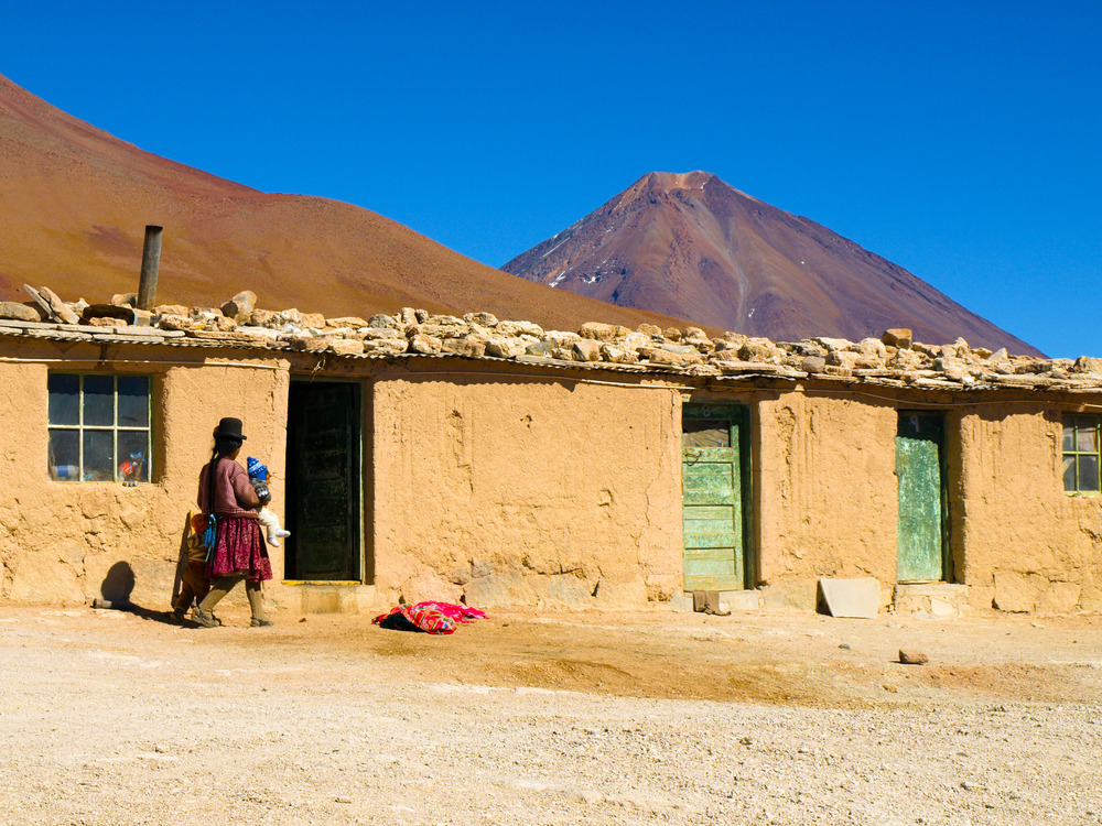 local bolivian woman in front of brown house altiplano
