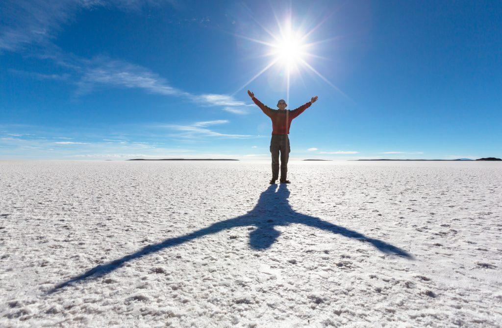 man with shade on salt flat bolivia