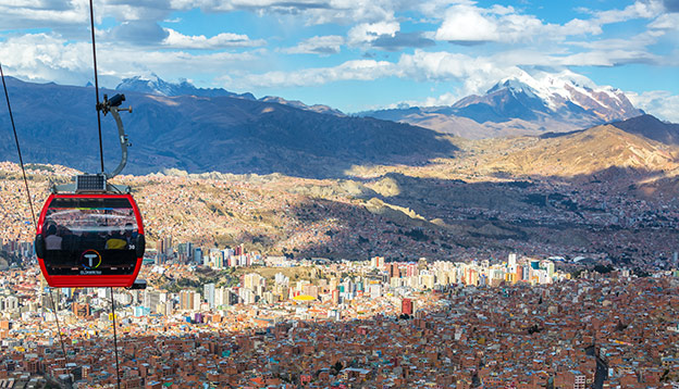 Red cable car travelling high above the city of La Paz, Bolivia.