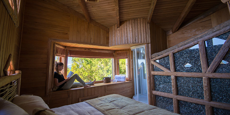 wooden lodge with double bed en woman sitting in the window