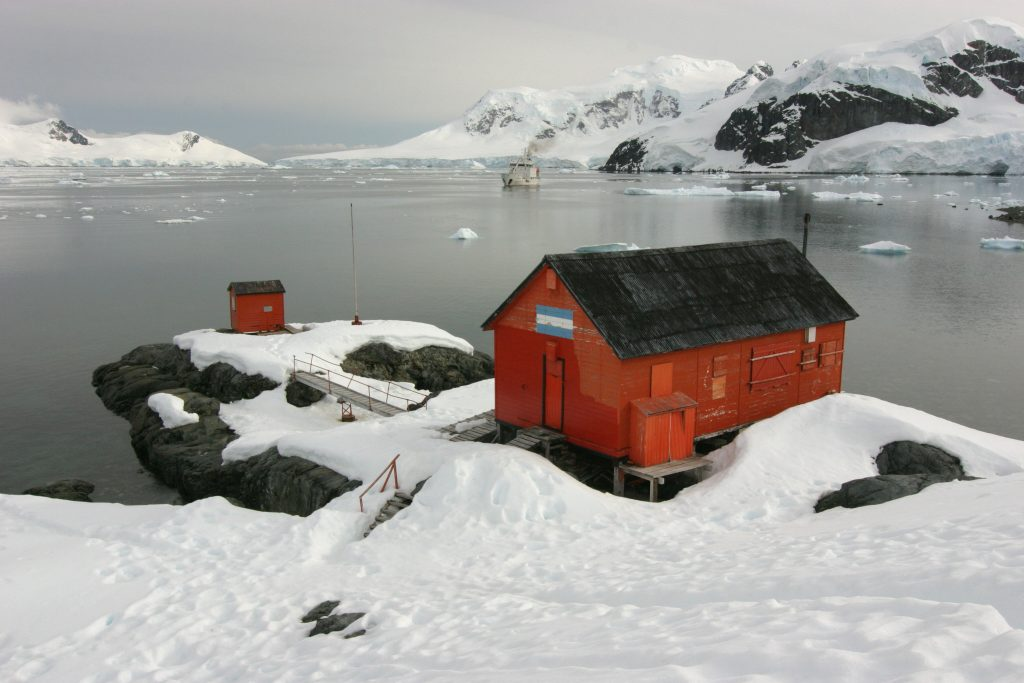 red buiding in the snow on antarctica next to the sea