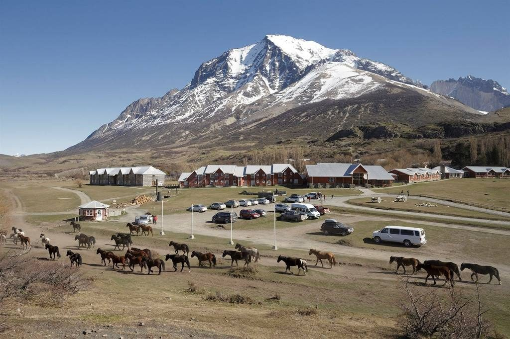 hotel with mountains in the backdrop and horses in the foreground