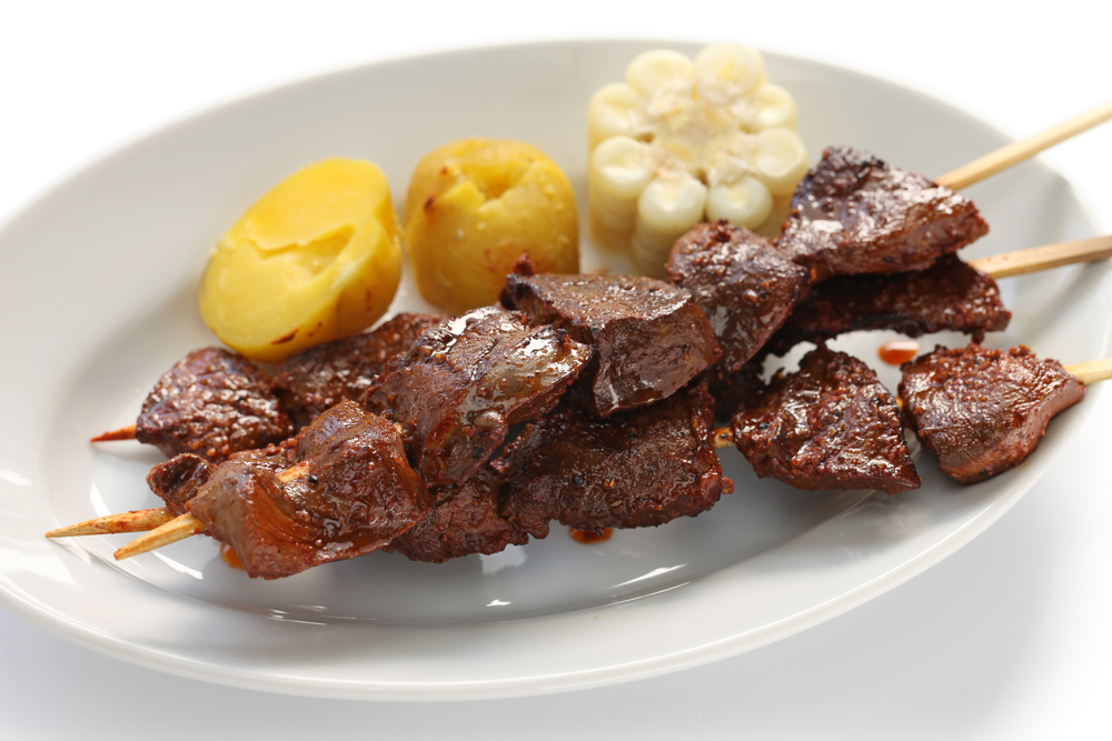 meat skewers on a white plate