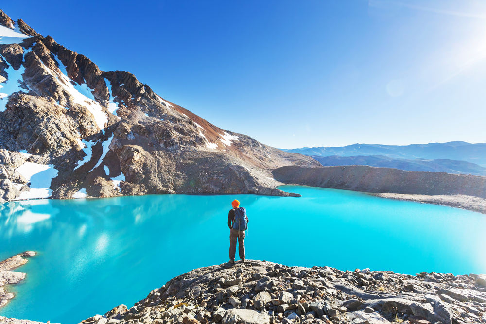 hiker on the edge of a blue lake with mountians in the backdrop patagonia