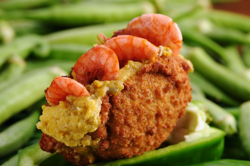 Acaraje a calorie rich snack with yellow on the inside and shrimps on top