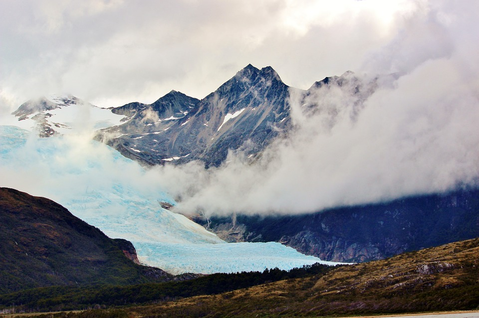 glacier betweeen snow capped mountains