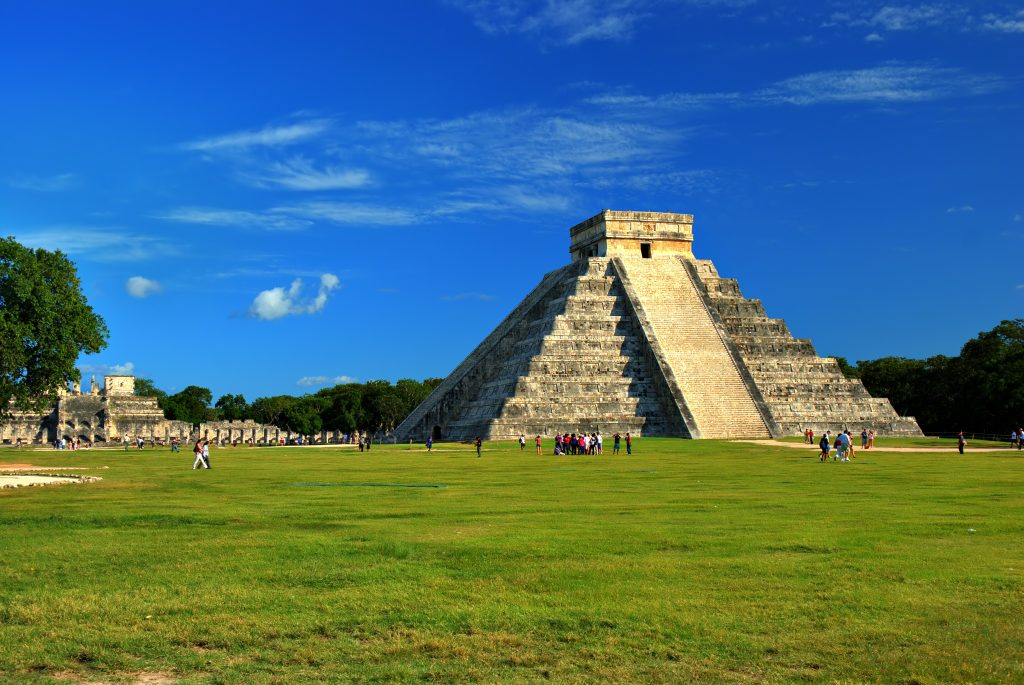 The Chichen Itza, ancient mayan ruin with green grass and blue sky.
