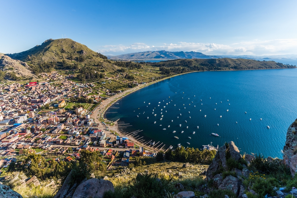 aerial view over the city copacobana and lake titicaca with mountains in the background