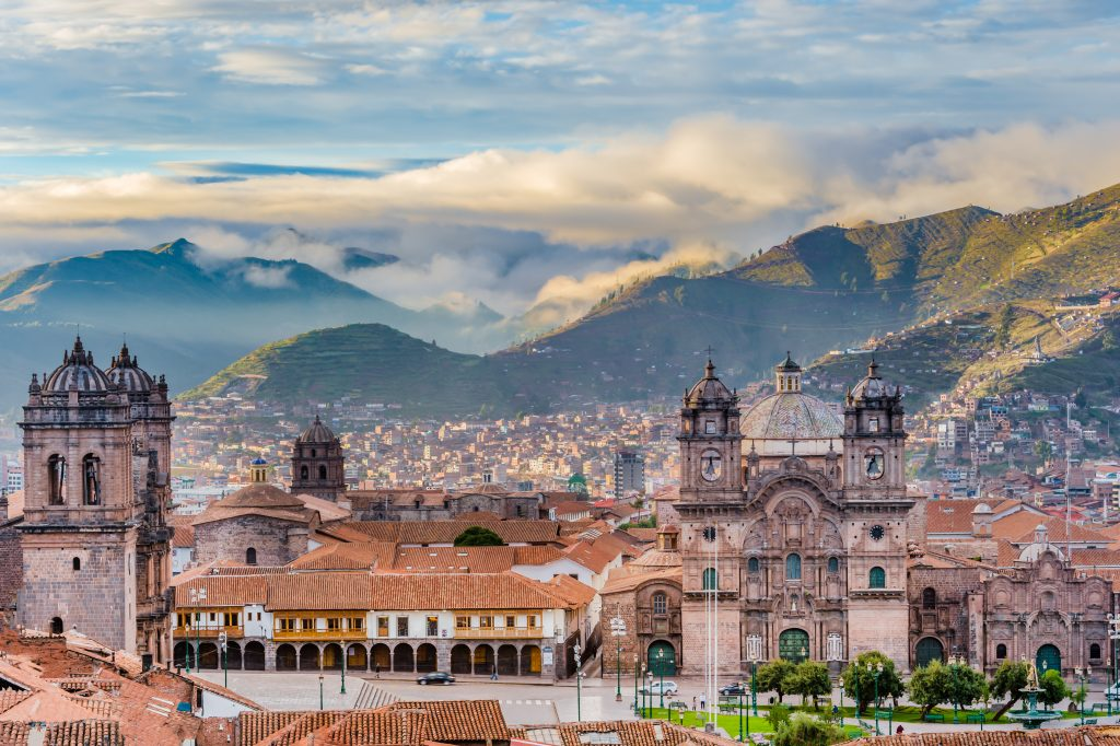 aerial view over the city of cusco with mountians in the background