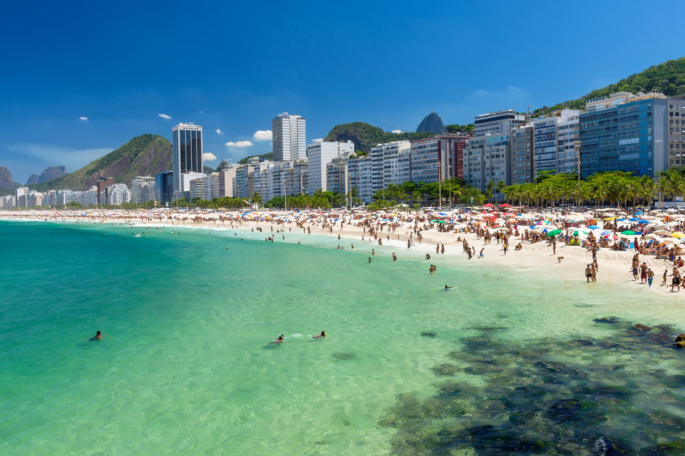 blue water and white sand beach with rio skyline