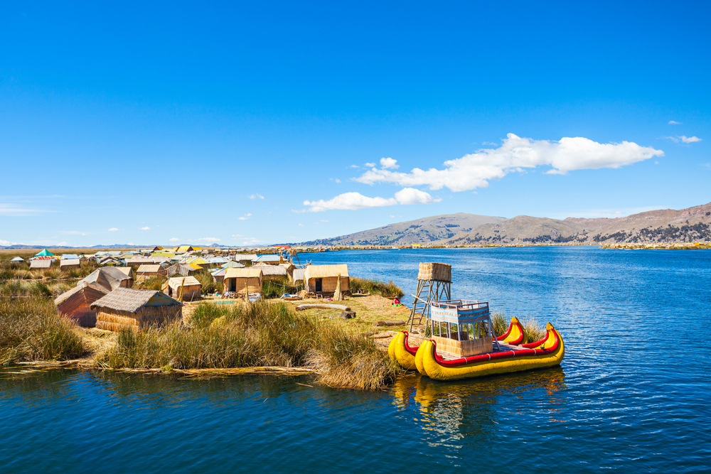 reed boats on lake titicaca with reed sheds in background