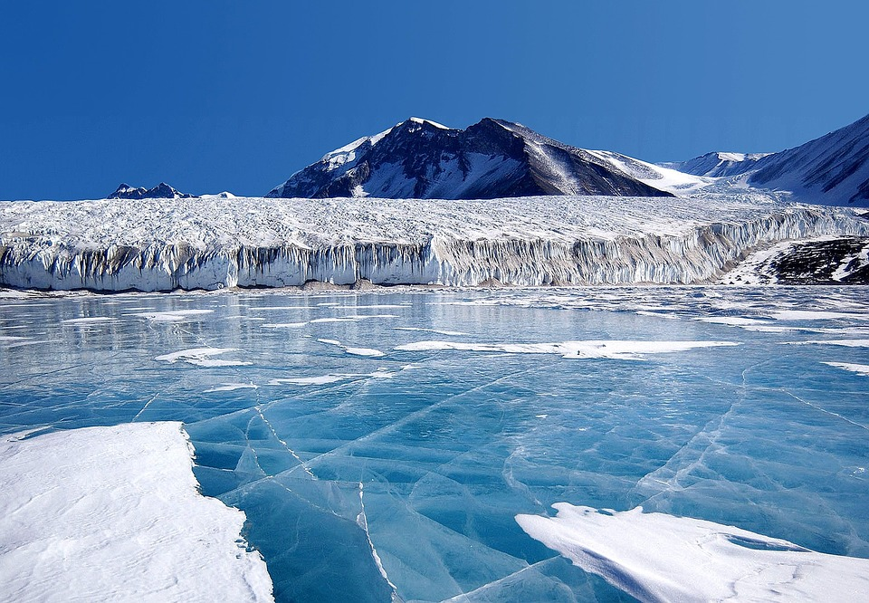 frozen sea with icebergs in background