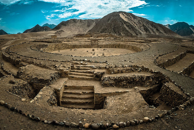 ancient ruin of Caral from above with mountain in background
