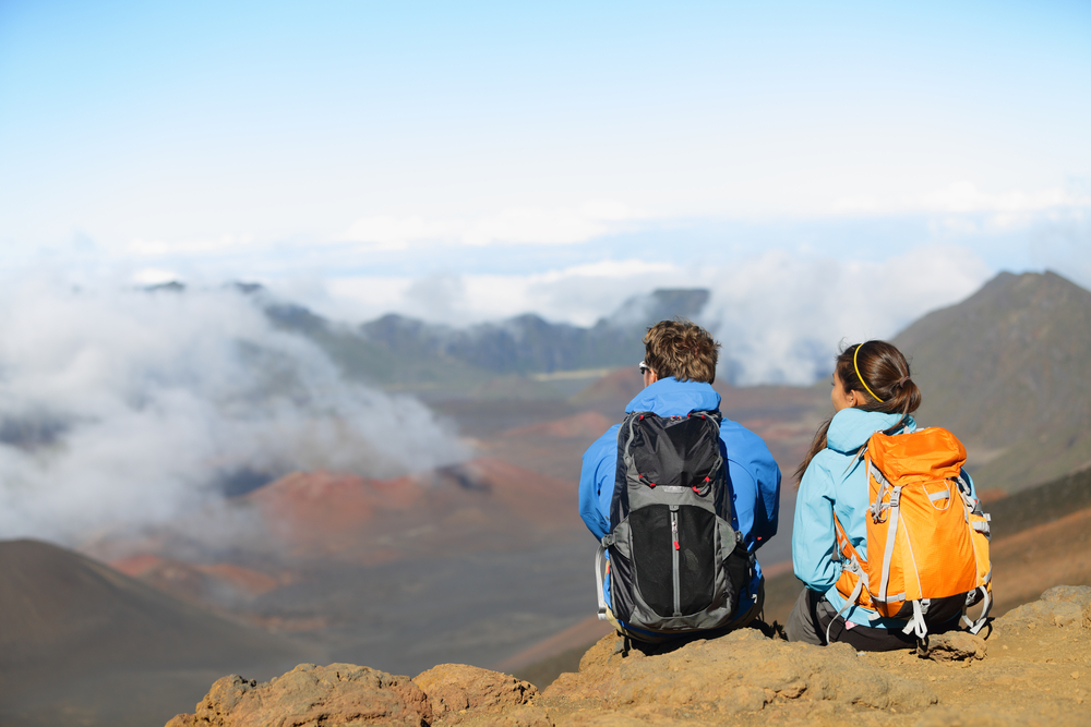 Hikers sitting on a rock with view over mountains