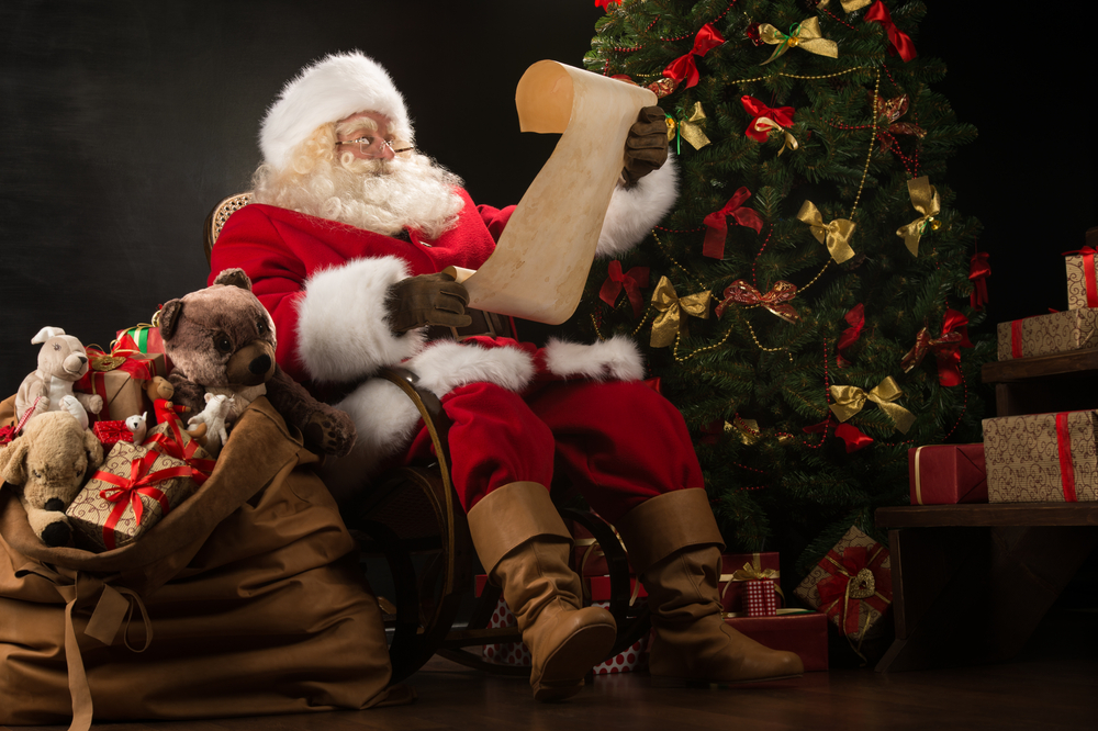 Santa claus reading from a paper next to a christmas tree