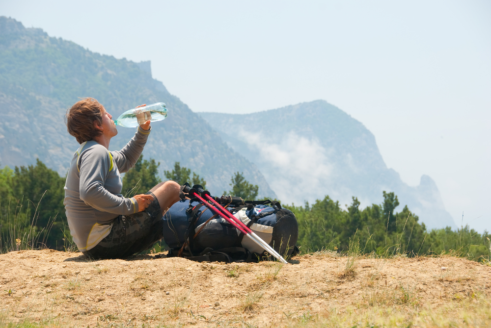 hiker drinking water from a bottle with mountains in the background