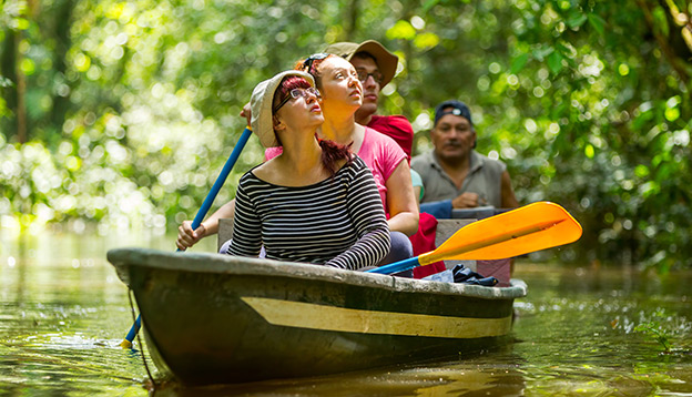 Tourists exploring the Amazon River by canoe