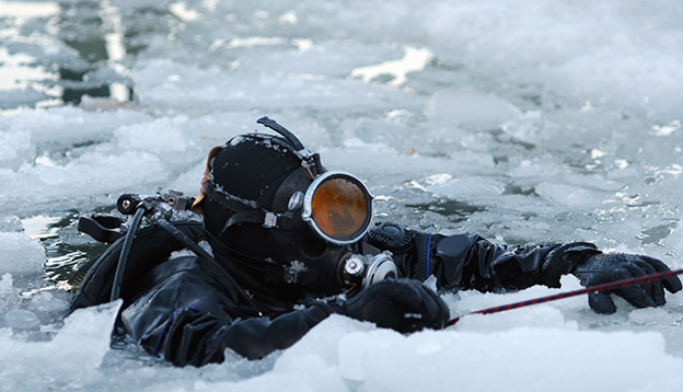 A scuba diver emerges through the icy waters of Antarctica