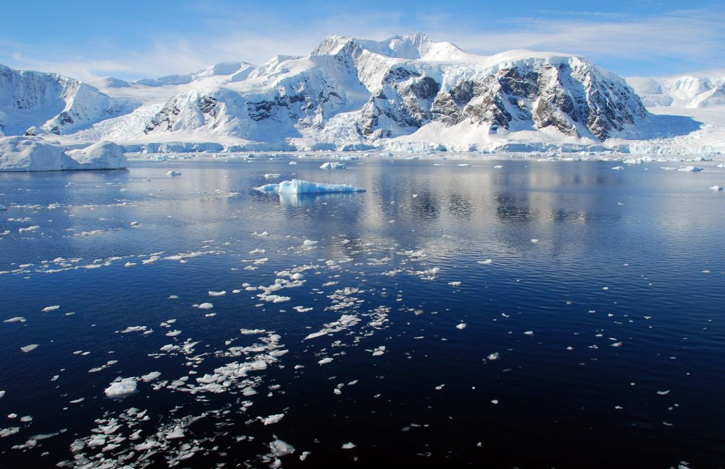 snow capped mountains in antarctica with sea in the foreground
