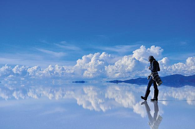 A tourist walks over Salar de Uyuni, Bolivia