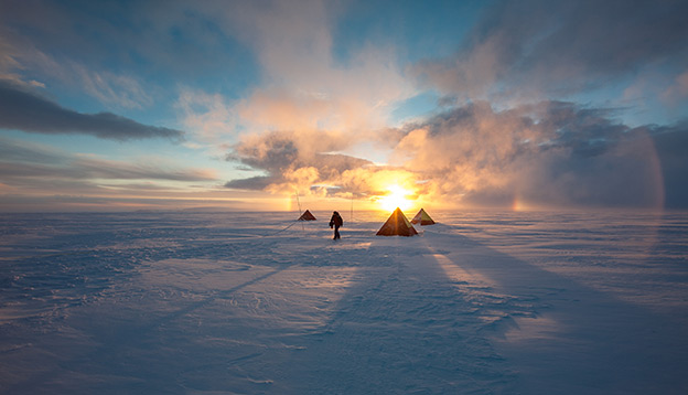 Antarctica Activities: People setting up tents with a sunset behind them.