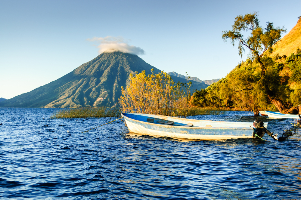 lake with boat on the water and volcanoe in the background