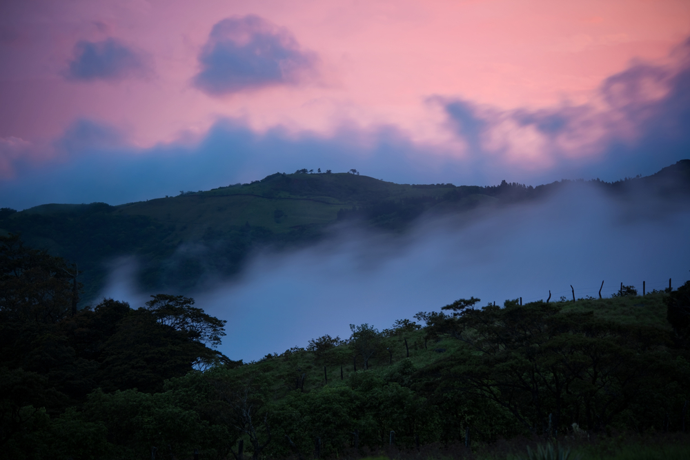 pink sunset over mountains in monteverde, costa rica with clouds