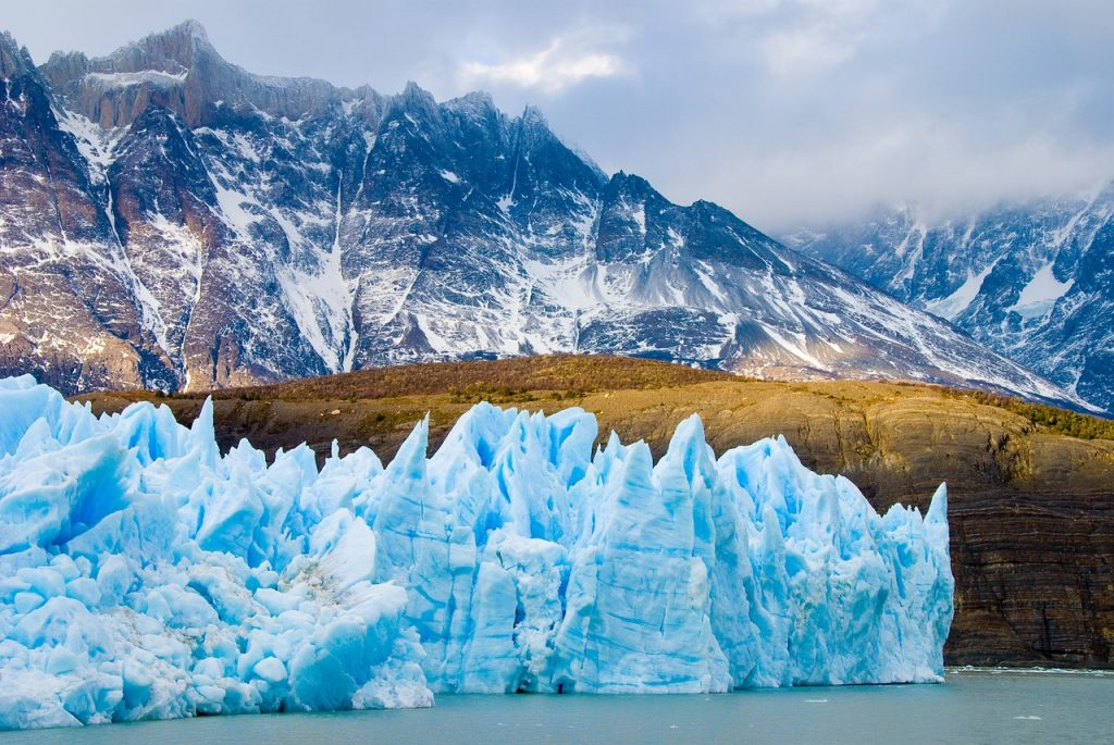 ice formations in front of snow capped mountains chile patagonia