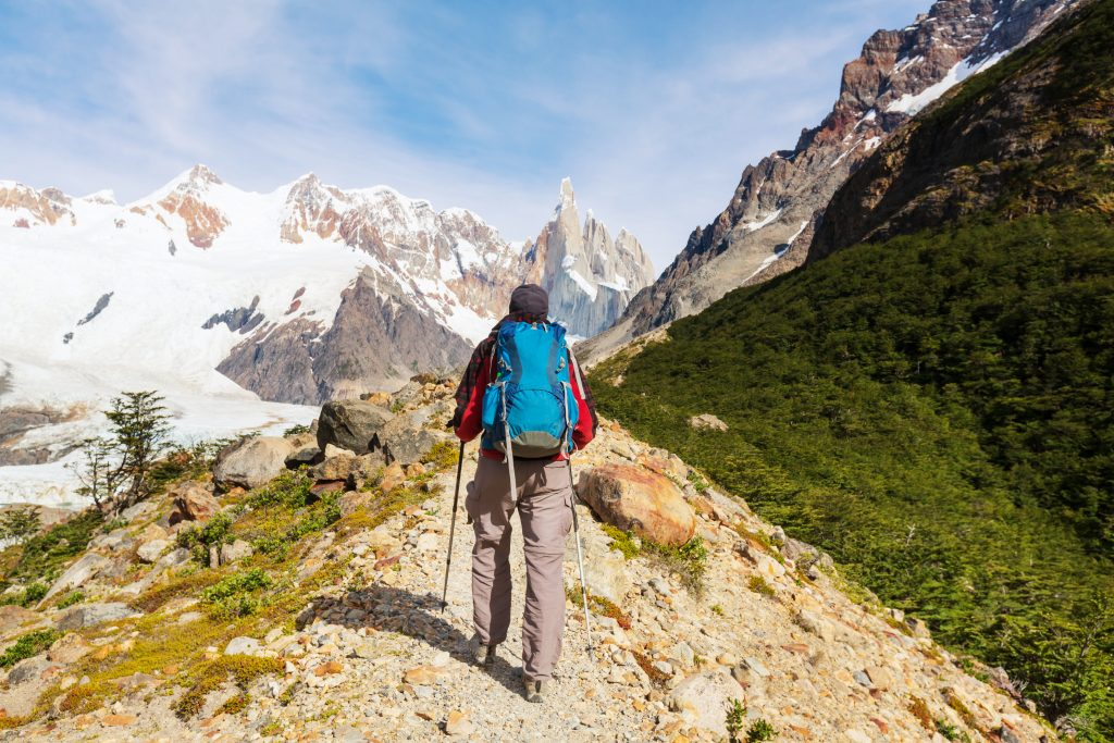 hiker on ridge with snow capped mountains in the background patagonia