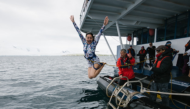 Antarctica Activities - person takes the polar plunge by jumping into the cold Antarctic waters.