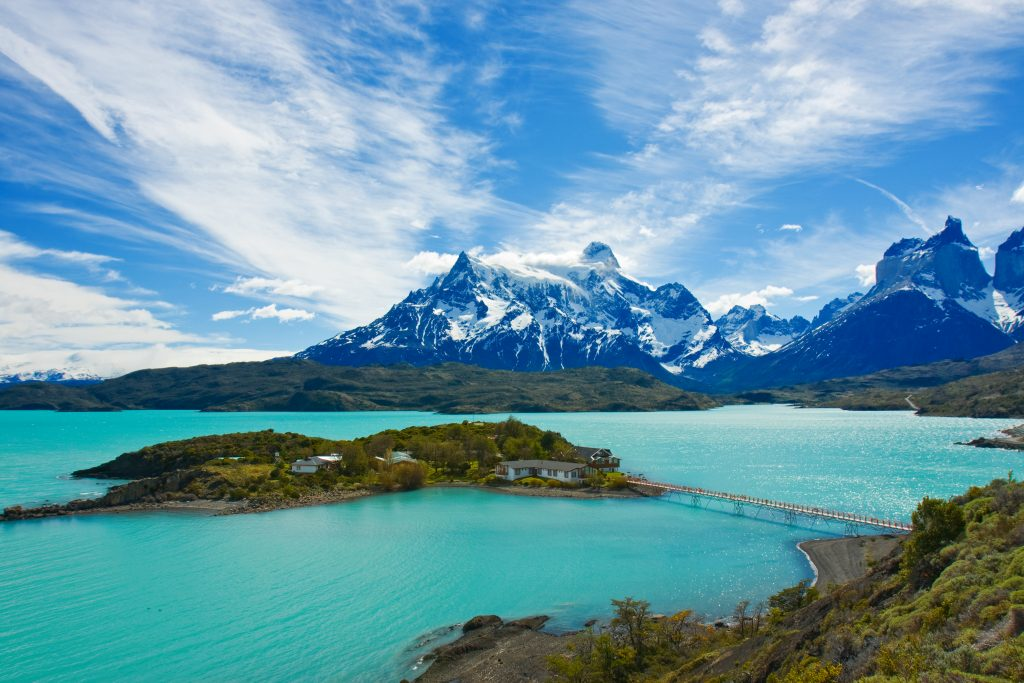 clear blue water lake with snow capped mountains around patagonia chile