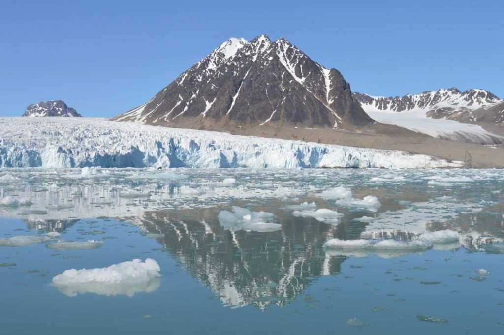 mountain in the arctic with ice shelf reflecting in sea
