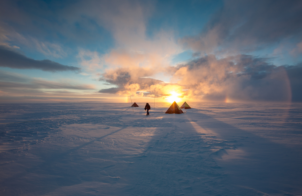 camping on ice field in antarctica with sunset