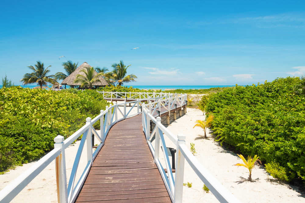 plan your South America Tour ; wooden pathway to the white sand beach cuba