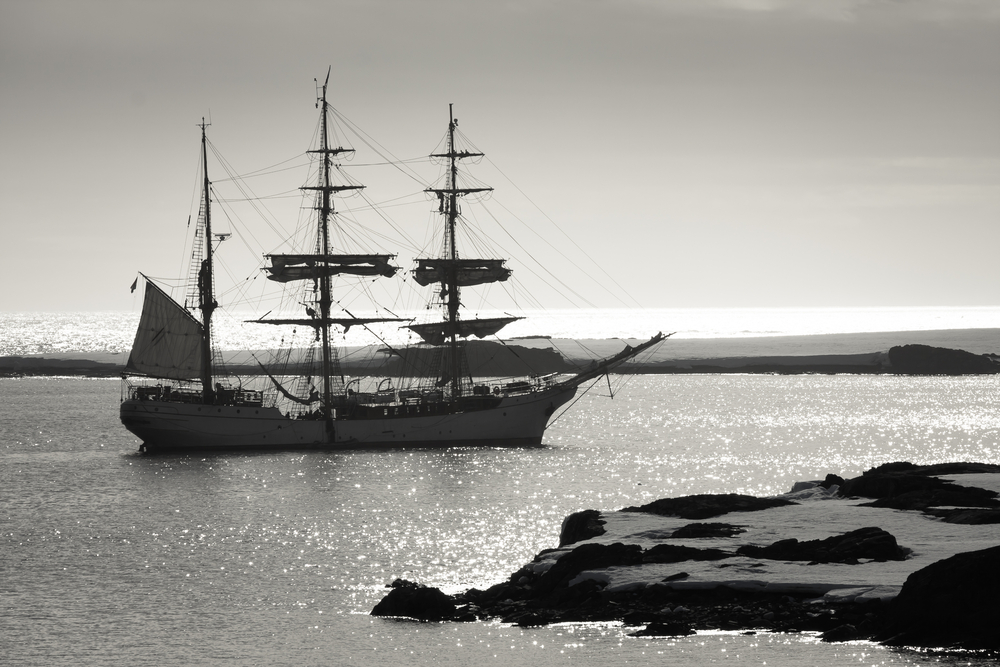 sailing ship in front of snowy coast