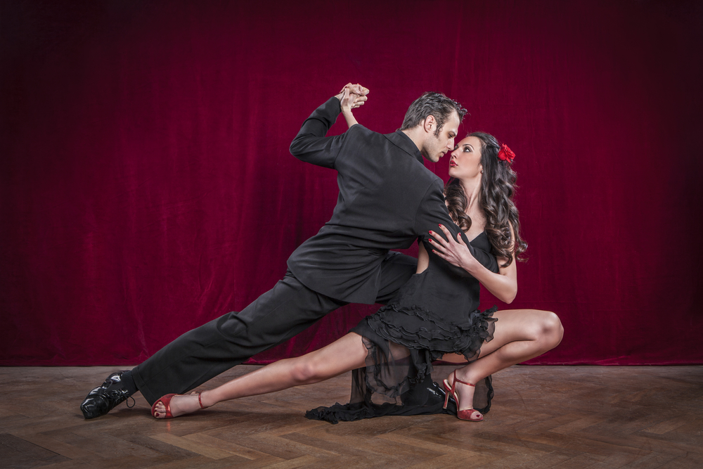 two dancers dancing tango with red background
