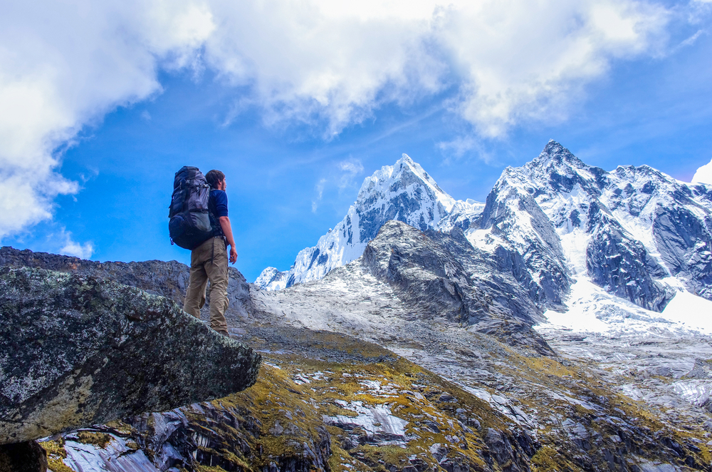 hiker in front of snow capped mountains in peru
