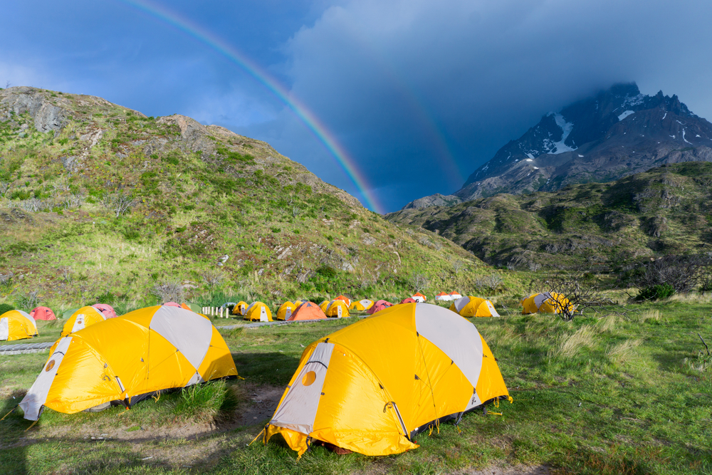 yellow tents on mountain with rainbow in the background