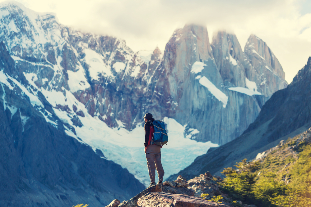 hiker in front of big rocky mountains patagonia